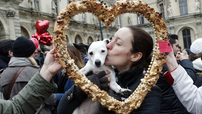 woman kissing dog at festival