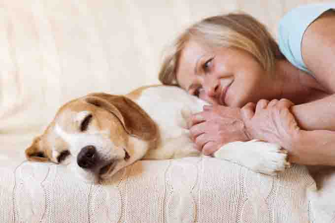 Woman comforts her dog on a white sofa.