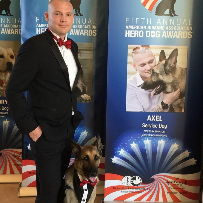 Jason and his German Shepherd service dog, Axel, stand in front of a banner for the American Humane Association's Hero Dog Awards.