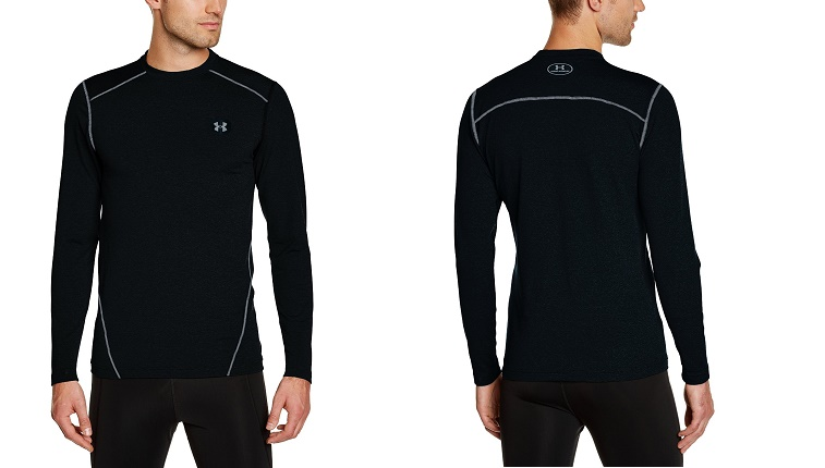 A man models black Under Armour clothing against a white background.