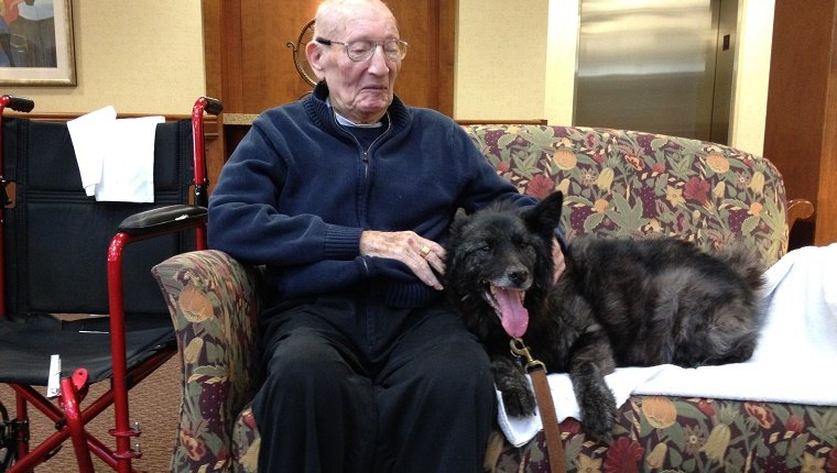 An elderly man sits on a couch with a black dog.