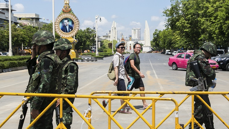 Military personnel stand next to a gate on a Thai street with an image of the king in the background.