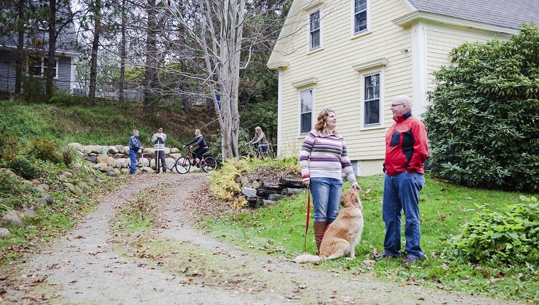 Two neighbors stand in front of a driveway with a Golden Retriever.