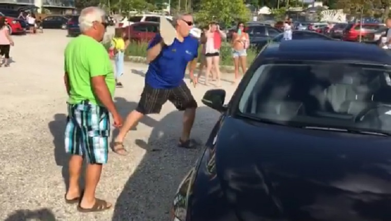 A man throws a rock at a BMW window