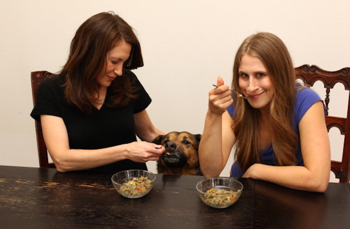 NEW YORK - FEBRUARY 23. EXCLUSIVE: Allison Weiner (L), Connor the dog and Hanna Mandelbaum eat the same meal on February 23, 2011 in New York City. Two business partners are literally making a dogs dinner of their work as they aim to eat a bowl of their pet food every day for a month. Hanna Mandelbaum, 30 and Allison Weiner, 38, who co-own Evermore Pet Food, have decided to prove their upmarket dog food is fit for human consumption by eating a portion every day for the month of March. Sitting down with a soup sized bowl filled with either chicken or beef flavour of their 'human grade' pet food, Hanna and Allison are literally putting their money where their mouth is by backing their product so publically. Eating the dog food as part of a healthy three meal a day diet, Hanna and Allison prove their month long experiment in canine cuisine by broadcasting each meal time on a webcam on their website. (Photo by James Ambler / Barcroft USA / Getty Images)