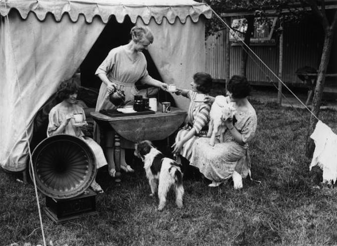 May 1923: Young ladies enjoying a cup of tea and music when camping on the Chiltern Hills. (Photo by Topical Press Agency/Getty Images)