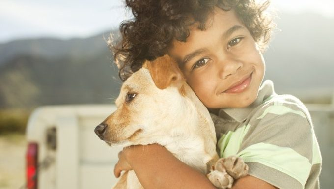 kid holding dog
