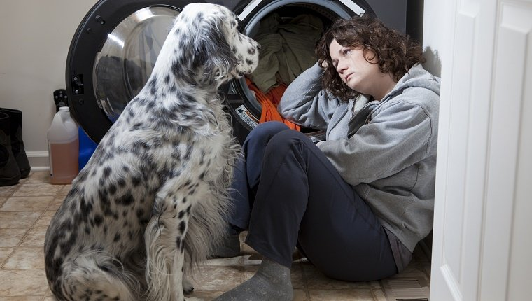 Woman crying on the floor while her dog tries to comfort her