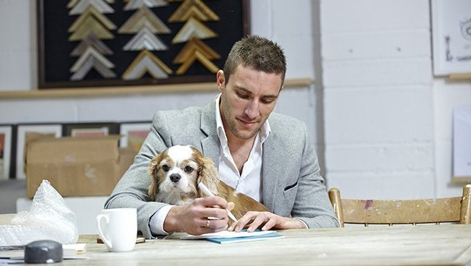 man writes with dog on lap