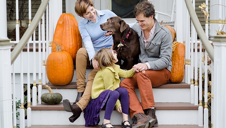 Happy Family Sitting In Front of House with Dog and Pumpkins