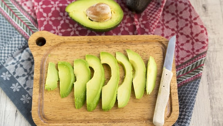 Sliced avocado and knife on chopping board