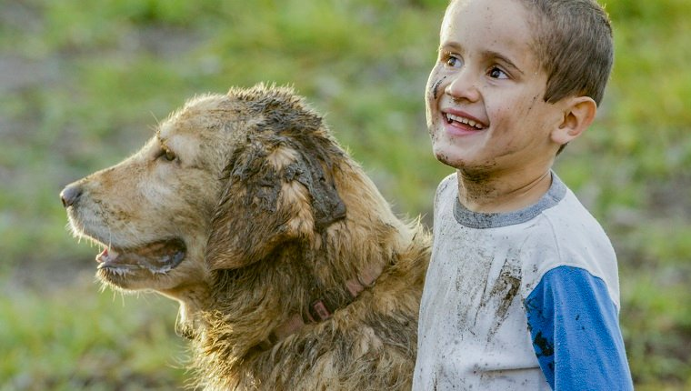 A young boy stands outside in the mud and pets his golden retriever. They play in mud and puddles outdoors on a farm on a warm fall day.