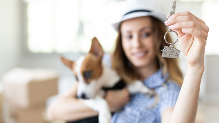 Woman with hat sitting in her new home and holding the keys.