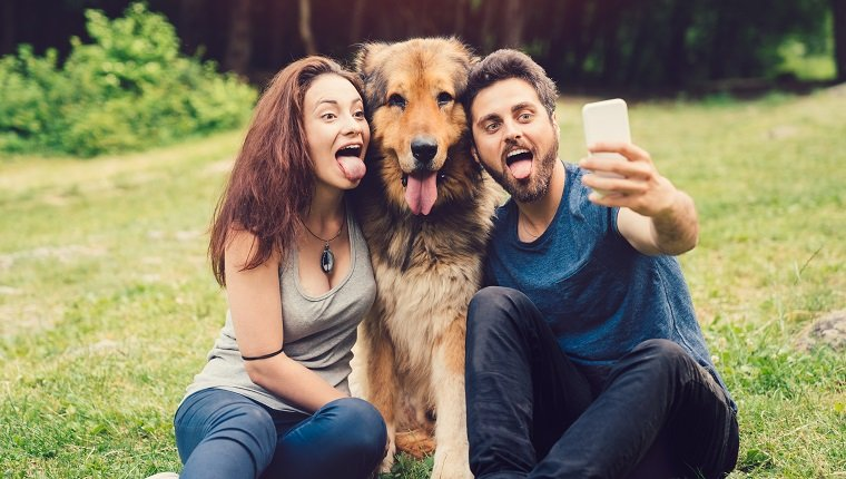 Young couple and dog sticking out tongues for a selfie at the countryside