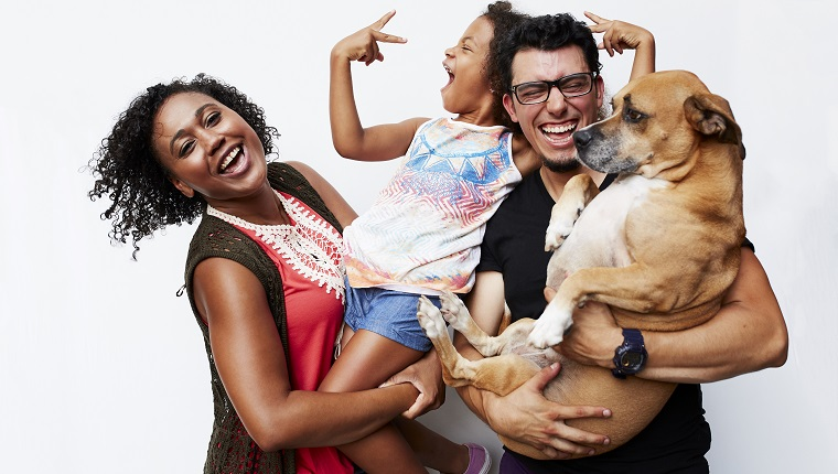 Man and woman holding daughter and dog