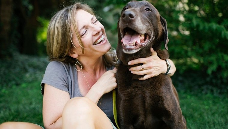 Smiling woman sitting on grass with Labrador Retriever