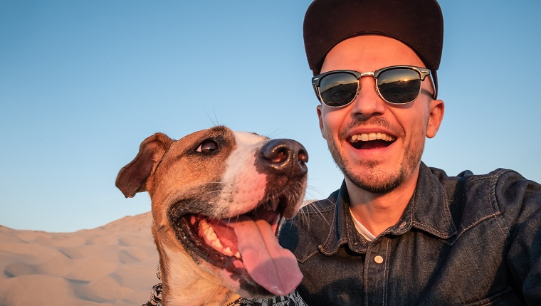 Happy young male person makes self portrait with his dog outdoors