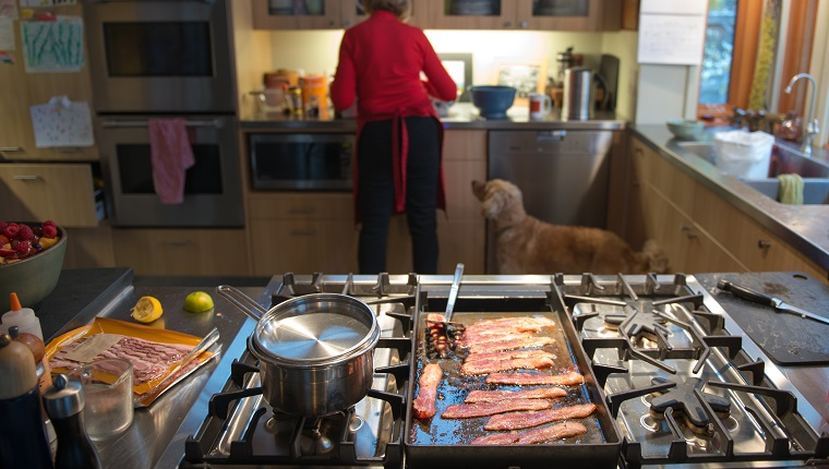 Grandmother in the kitchen prepares a brunch of bacon and eggs as her dog watches her mixing ingredients with interest.