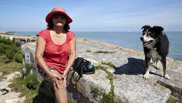 Senior hispanic woman with dog on sea wall