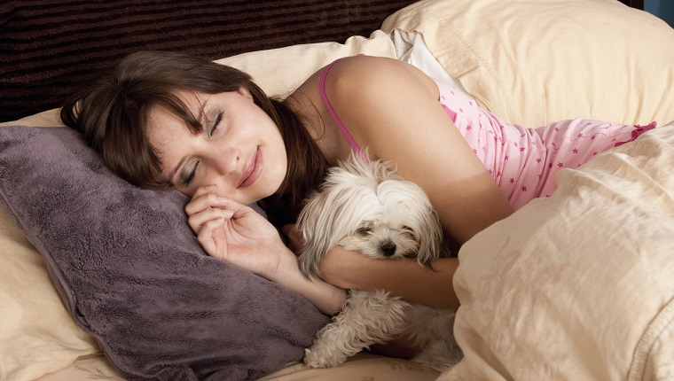 a woman and dog sleep in bed
