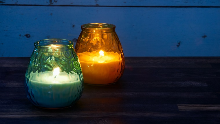 Blue and yellow citronella candles lit in the garden are being used to keep mosquitoes at bay in the late evening